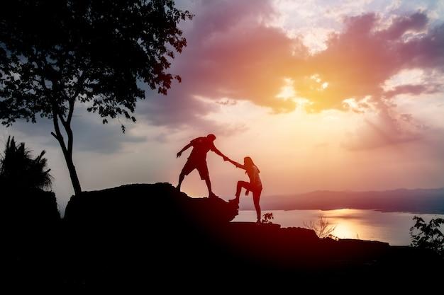 Silhouetten van twee mensen die op berg en het helpen beklimmen. Premium Foto