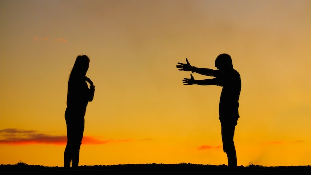 Silhouettenparen op zonsonderganghemel Premium Foto