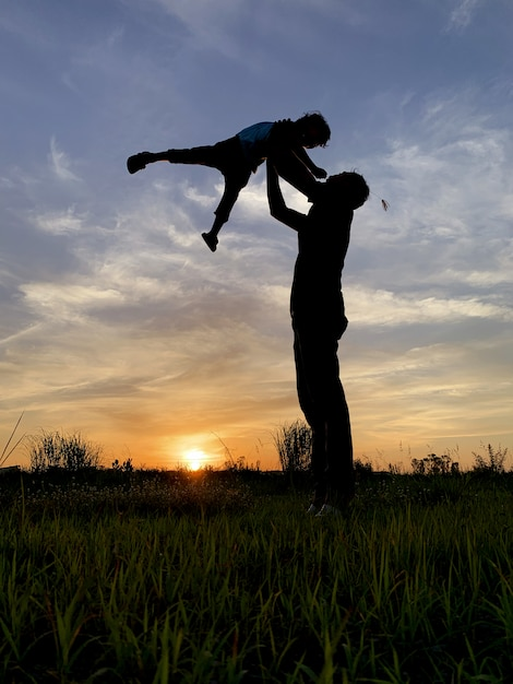 Silhouetvader carrying son against sky tijdens zonsondergang Premium Foto