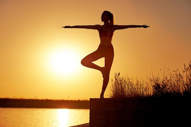 Silhouetvrouw het praktizeren yoga of het uitrekken zich op de strandpijler bij zonsondergang of zonsopgang Premium Foto
