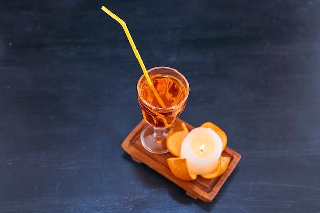 Sinaasappel en een glas sap met gele pijp op houten schotel, hoekmening Gratis Foto