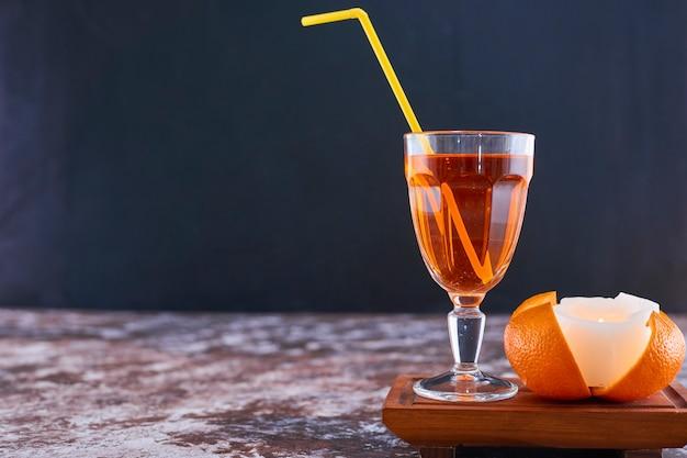 Sinaasappel en een glas sap met gele pijp op houten schotel op marmer Gratis Foto