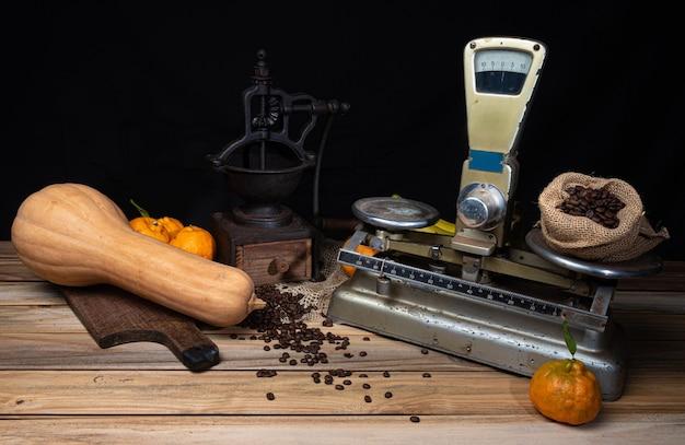 Sinaasappelen, bananen, een pompoen en oude accessoires op hout Premium Foto