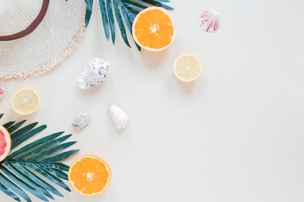 Sinaasappelen met palmbladeren, schelpen en strohoed Gratis Foto