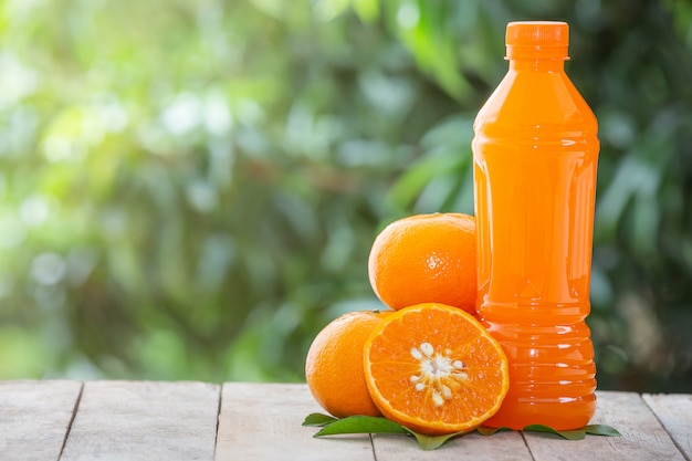 Sinaasappelsap in een fles en sinaasappels Gratis Foto
