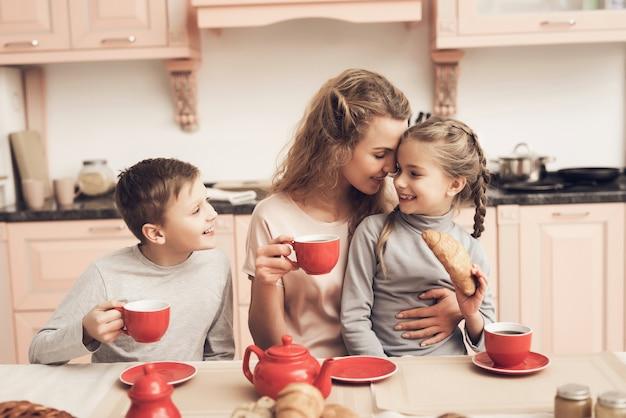 Single parent mum kids hebben thee met croissants. Premium Foto