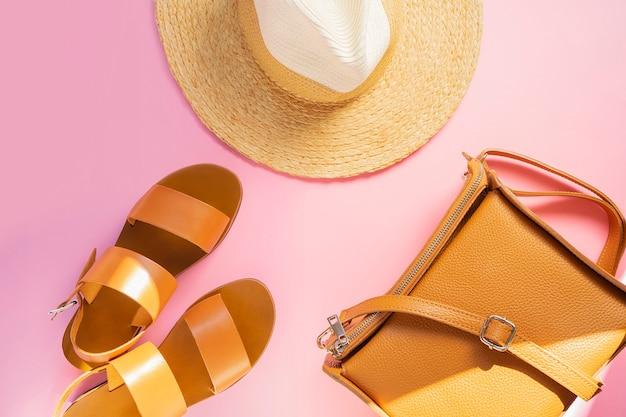Sjabloon met bruin lederen sandalen, strooien hoed en zand kleur tas op roze achtergrond. vrouwelijke accessoires. zomer reizen vakantie concept. uitverkoop kit. kopieer ruimte. Premium Foto