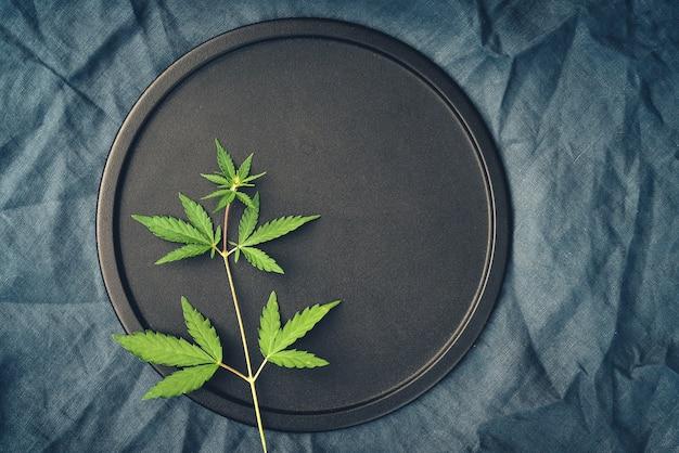 Sjabloon met een struik marihuana op een donkere achtergrond voor het plaatsen van medicinale cannabisproducten met cbd-olie Premium Foto