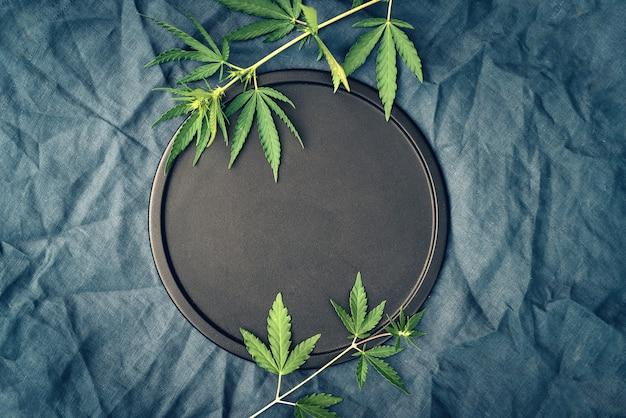 Sjabloon met marihuanabladeren op donkere achtergrond voor cannabisproducten, cbd-olie Premium Foto