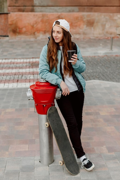 Skateboarder meisje met een kopje koffie wegkijken Gratis Foto
