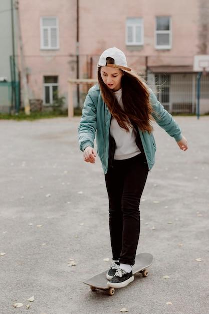 Skater meisje haar skateboard rijden Gratis Foto
