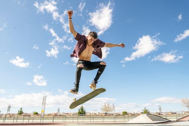 Skater met skateboard doet truc in skatepark Premium Foto