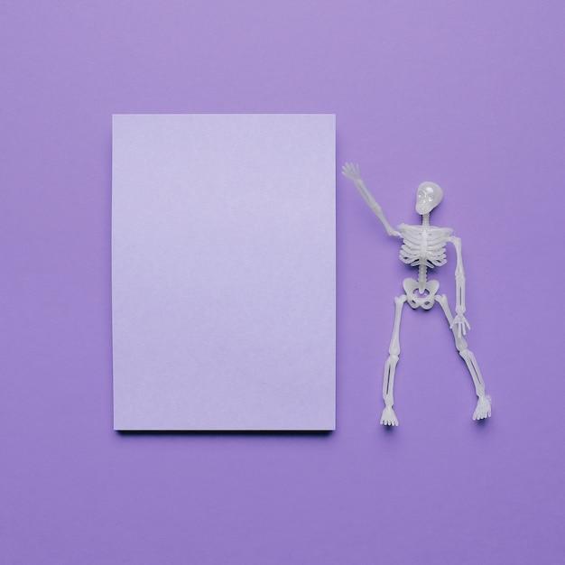 Skelet dat een lege ruimte voor tekst met halloween-vibes richt Gratis Foto