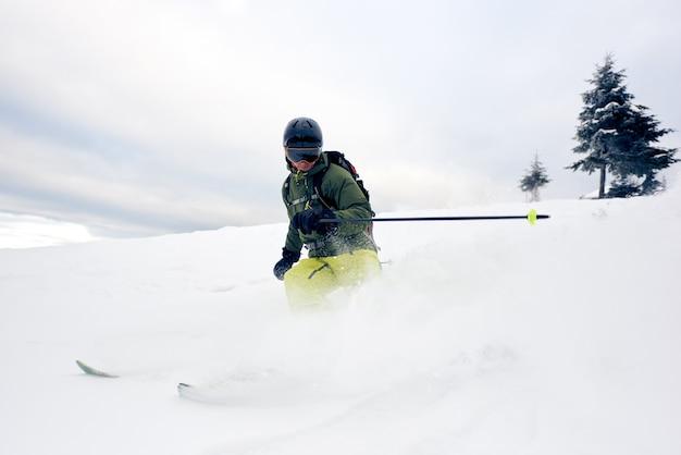 Skiër in diepe poeder op met sneeuw bedekte bergafwaarts. extreem skiën concept. grijze lucht en pijnboom op achtergrond. vooraanzicht. Premium Foto