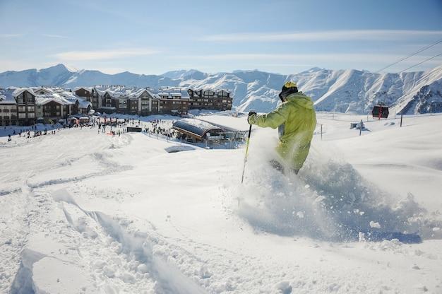 Skiër in gele sportkleding rijden de helling af in georgië, gudauri Premium Foto