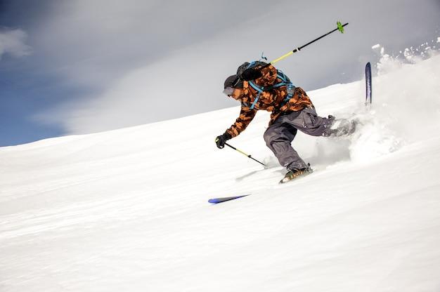 Skiër in kleurrijke sportkleding rent de berg af met ski's en skistokken Premium Foto