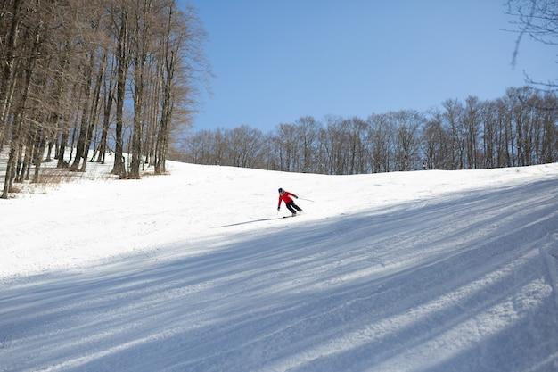 Skiër in rode jas bergaf skiën tijdens zonnige dag in het hooggebergte Premium Foto