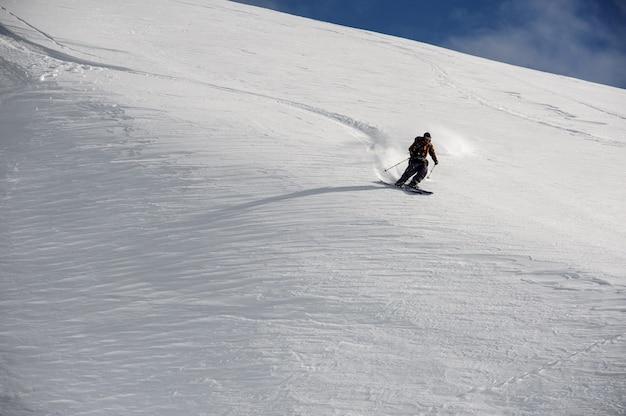 Skiër in speciale sportkleding glijdt bij helder weer snel de bergen af Premium Foto