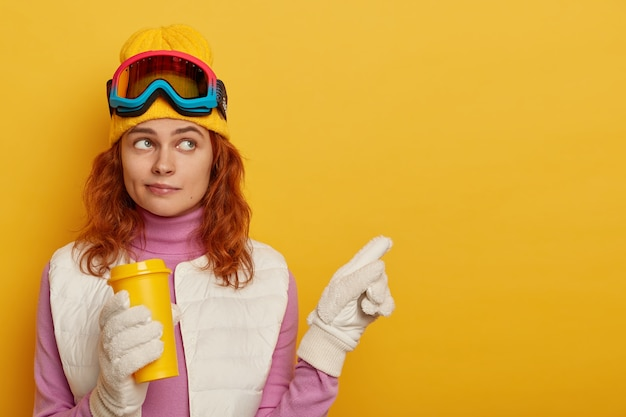 Skiër met rood haar, draagt gele hoed, wijst op een lege plek, houdt afhaalkoffie vast, demonstreert winterlandschap, staat tegen gele achtergrond Gratis Foto