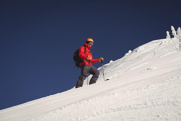 Skiër skiën in besneeuwde alpen Gratis Foto