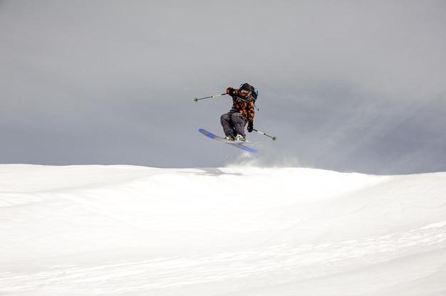 Skiër springt hoog in de lucht terwijl hij bij bewolkt weer van de berg glijdt Premium Foto