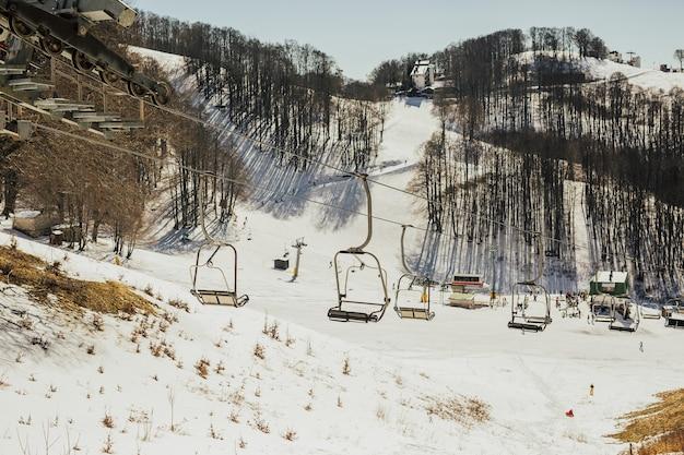 Skigebied, helling, skiërs op de piste onder witte sneeuw. Premium Foto