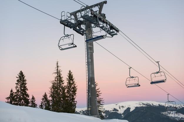 Skiliftstoelen op de wintertoevlucht tegen een mooie hemel bij zonsondergang Premium Foto
