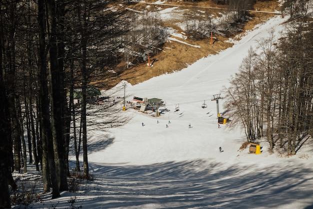 Skisporen op sneeuw bij alpiene bergheuvel. skiërs skiën in skigebied. Premium Foto