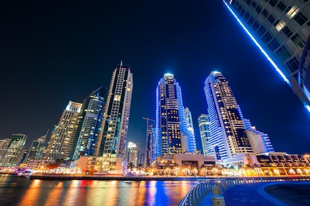 Skylinesmening die van de jachthaven van doubai in nacht tonen Premium Foto