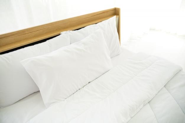 Slaapkamer ingericht in minimalistische stijl, foto van witte kussens en houten bed in de slaapkamer met natuurlijk licht vanuit het raam. Premium Foto