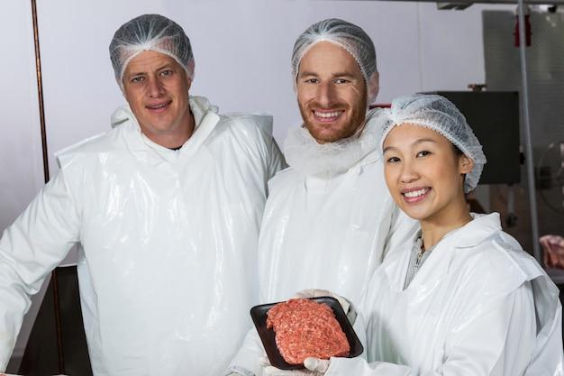 Slager die ruwe vleespasteitjes houdt die in dienblad worden geschikt Premium Foto