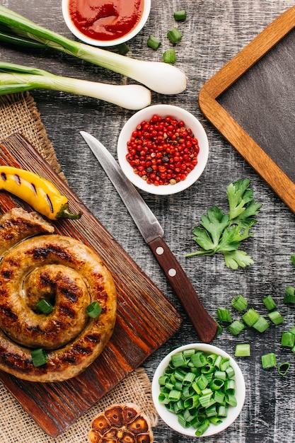 Slakworst met groente op grijze achtergrond Gratis Foto