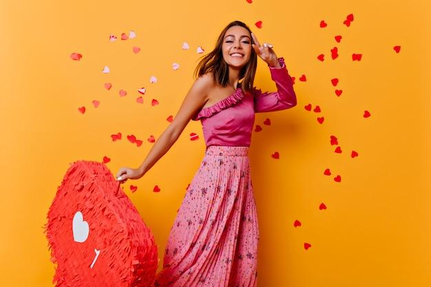 Slank gelooid meisje in trendy blouse dansen. geïnteresseerde jonge dame in roze kleren die zich voordeed op gele muur. Gratis Foto