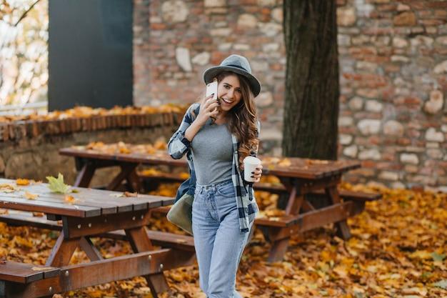 Slank meisje in blauwe denim broek praten over de telefoon in park met bomen achter Gratis Foto