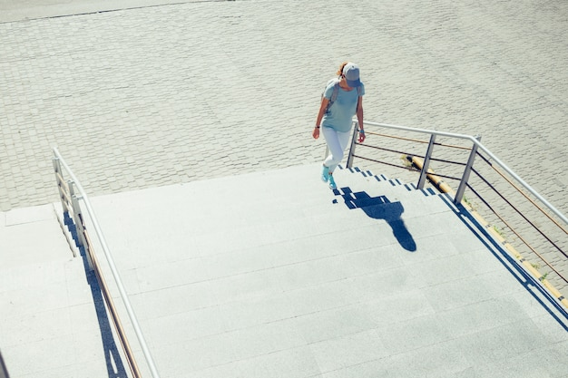 Slank meisje in een glb en jeans die treden in de stad in de zomer beklimmen Premium Foto