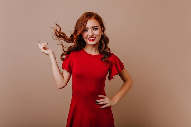 Slanke blanke vrouw in een rode jurk lachen. schitterend gember meisje speelt met haar haar tijdens fotoshoot. Gratis Foto
