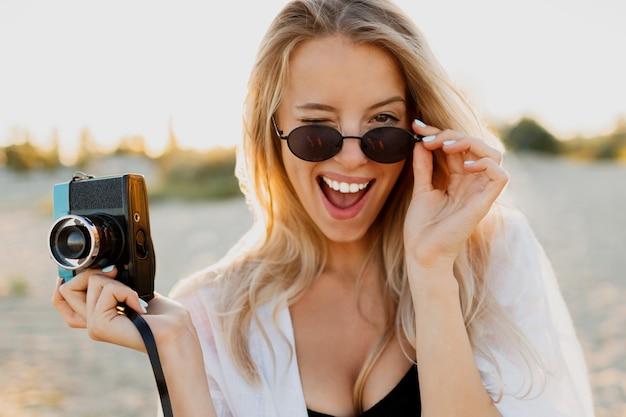 Slanke blonde gelukkige vrouw die retro camera houdt en pret op warm zonnig strand heeft. zomervakantie en reizen concept. natuurlijke schoonheid, vakantie in azië. trendy zonnebril, witte outfit. Gratis Foto
