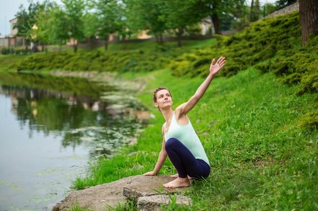 Slanke jonge brunette yogi voert geen ingewikkelde yoga-oefeningen op het groene gras in de zomer uit tegen de achtergrond van de natuur Premium Foto