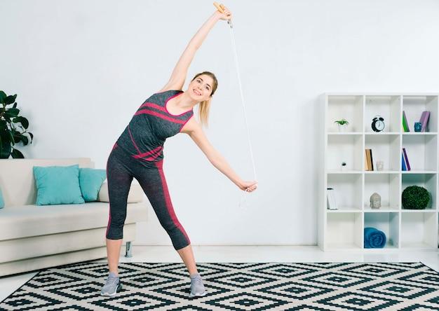 Slanke jonge vrouw die zich uitstrekt met haar springtouw staande in de woonkamer Gratis Foto