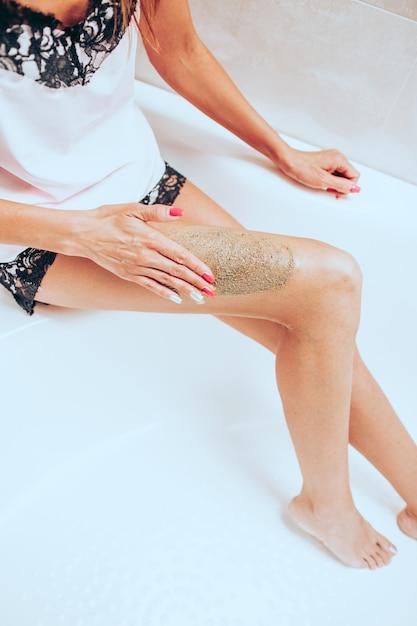 Slanke jonge vrouw in een lichte zijden pyjama krabt haar beenzitting in een groot mooi helder bad Premium Foto