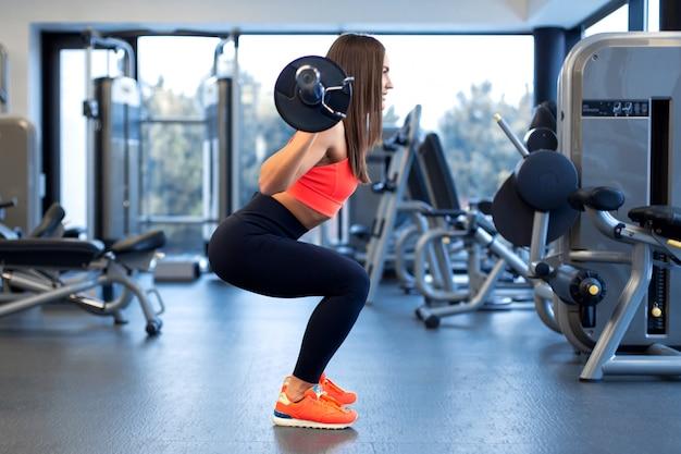 Slanke knappe jonge vrouw in sportkleding squats met een halter op de schouder in de sportschool Premium Foto
