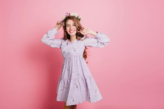 Slanke lieve vrouw in paarse jurk met plezier in de studio Gratis Foto