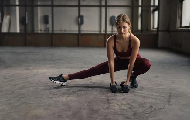 Slanke sportvrouw van het volledige lichaam kant lunge met halters doen tijdens fitnesstraining in ruime sportschool Premium Foto