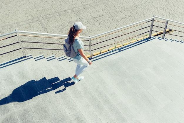 Slanke vrouw in een pet en met rugzak loopt in de zomer de trap af naar de stad Premium Foto