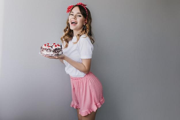 Slanke witte dame in romantische outfit poseren met verjaardagstaart. binnenfoto van spectaculair meisje dat vóór partij glimlacht. Gratis Foto