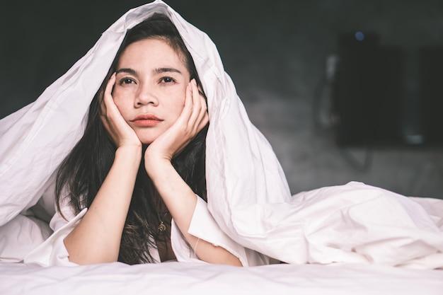 Slapeloze aziatische vrouw moe in bed Premium Foto