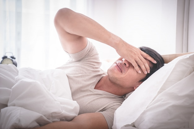 Slapeloze kater man op bed werd wakker met hoofdpijn Premium Foto