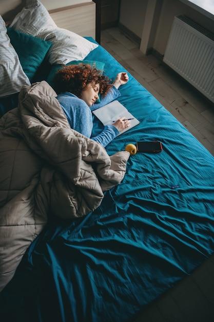 Slapende blanke vrouw met krullend haar die zich moe voelt na het doen van huiswerk met een pen en rust in de buurt van een boek en mobiel Premium Foto
