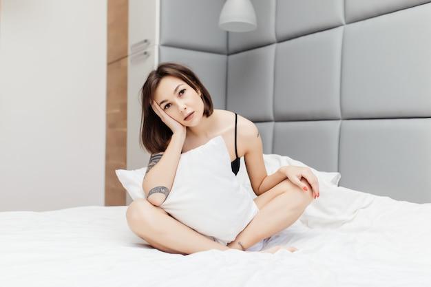 Slaperige brunette toont 's ochtends een ongezonde blik in haar brede bed Gratis Foto