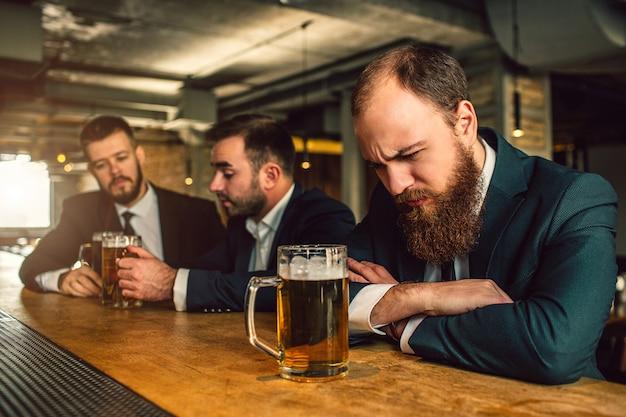 Slaperige jonge man slapen op toog. er zijn bierpul. twee andere mannen zitten achter en praten. ze hebben een mok bier twee. Premium Foto
